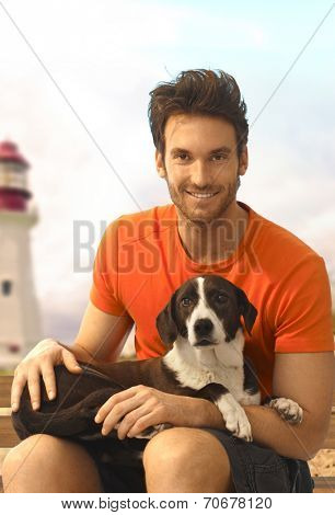 Happy handsome casual caucasian bristly guy sitting with dog laying in lap at the beach. Wearing shorts and t-shirt, looking at camera, smiling. Light tower in background.