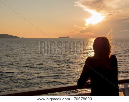 Girl looks at the sunset on the sea from the deck of a cruise boat. Corsica, mediterranean sea, France, Europe.