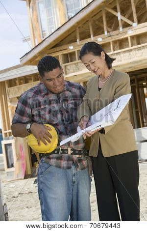 Construction worker studying blueprint with surveyor