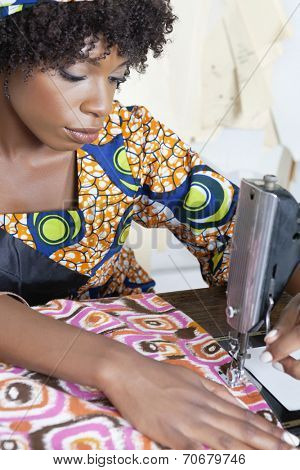 African American female tailor stitching patterned cloth on sewing machine