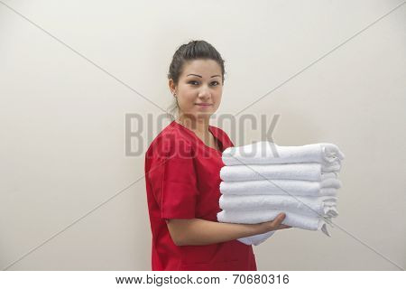 Portrait of female housekeeper holding clean white towels against gray background