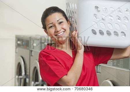 Portrait of a happy female employee carrying laundry basket
