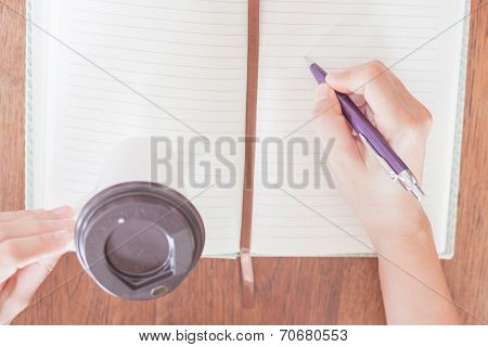 Woman's Hand Writing On Notebook