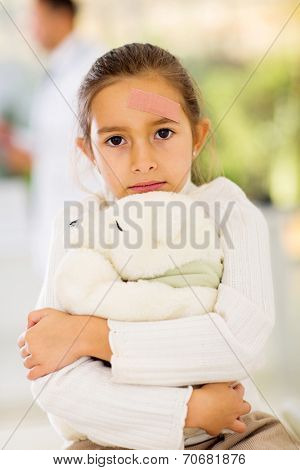 injured girl with band-aid on her forehead in hospital