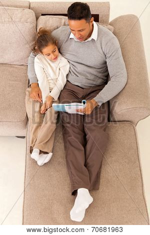 top view of father reading a book to his daughter in living room