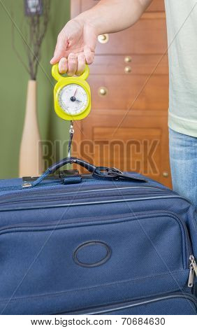 Woman checking luggage weight with a hand balance