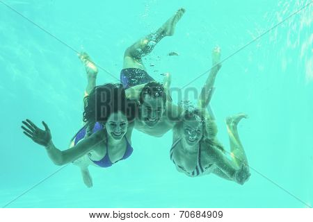 Group of young friends underwater in swimming pool