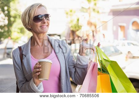 Happy mature woman walking with her shopping purchases on a sunny day