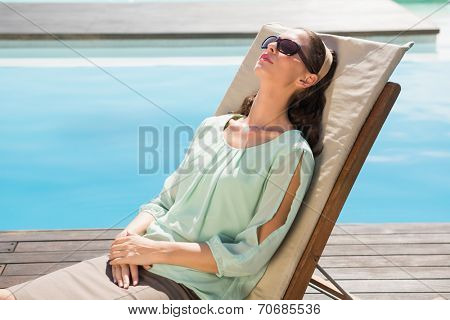 Side view of a beautiful young woman relaxing on sun lounger by swimming pool