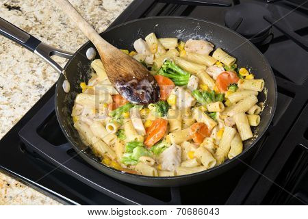 Freshly cooked pasta with vegetables, chicken and cream sauce in a stove top simmering pan