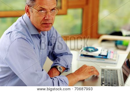Portrait of senior caucasian man working on his laptop computer.