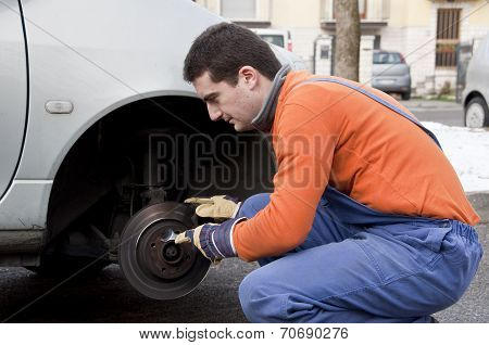 Mechanic Hand On Worn Car Brake