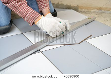 Tiler marks the tile during the floor installation