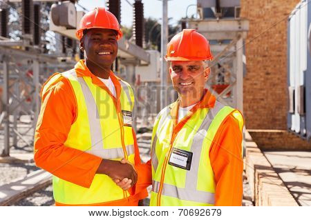 portrait of technical co-workers hand shaking in power plant