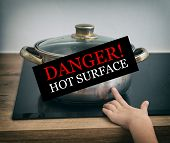 picture of dangerous situation  - Child touches hot pan on the stove. Dangerous situation at home.