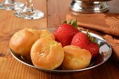 picture of cream puff  - A plate of mini cream puffs and strawberries on a rustic wooden table  - JPG