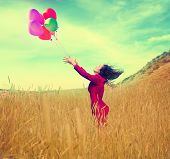 foto of wheat-free  -  a girl walking in a field letting go of a bunch of balloons done with a vintage retro instagram filter effect - JPG