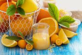 stock photo of curd  - Lemon curd in a small jar with fresh citrus fruits and leaves - JPG