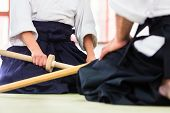 picture of aikido  - Man and woman fighting with wooden swords at Aikido training in martial arts school  - JPG