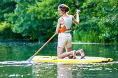 picture of paddling  - Woman paddling with surfboard sup on forest river - JPG