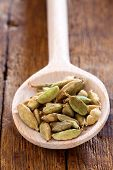 picture of cardamom  - Wooden spoon with green cardamom pods on rustic wooden table