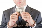 picture of white collar crime  - Withe collar crime with handcuffs and currency in his hands - JPG
