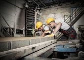 foto of heavy equipment operator  - Worker and foreman in a safety hats performing quality check on a factory   - JPG