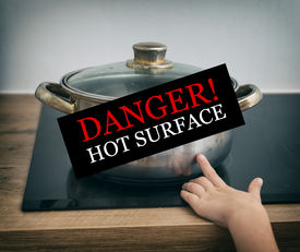stock photo of dangerous situation  - Child touches hot pan on the stove. Dangerous situation at home.