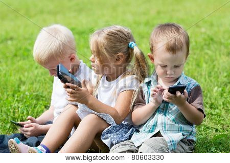 Cute children using smartphones sitting on the grass in the park. Brothers and sister.