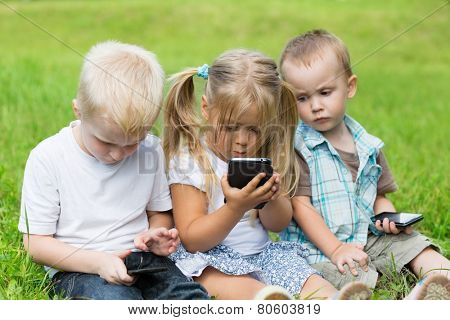 Kids playing on smartphones sitting on the grass in the park. Brothers and sister.
