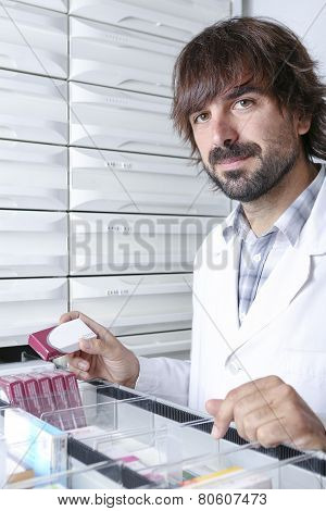 Male Pharmacist At The Pharmacy Store.