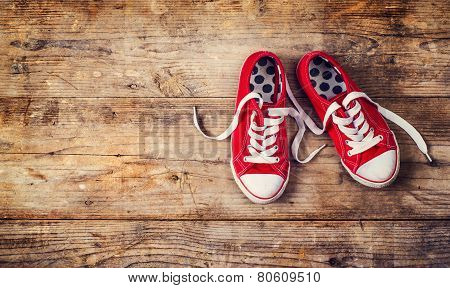 Red sneakers on a wooden floor