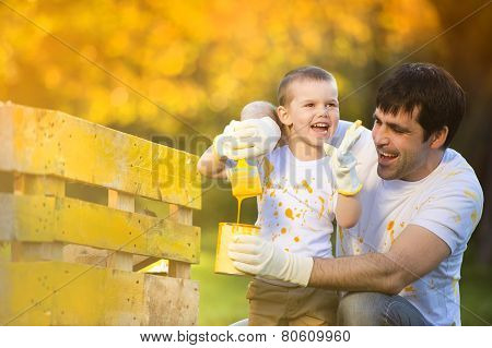Father and son painting fence