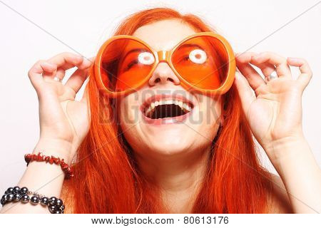Young funny redhair woman in big orange glasses
