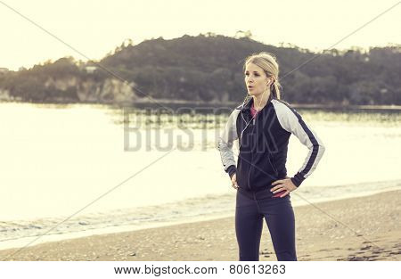 Female runner listening to music while getting ready for a run
