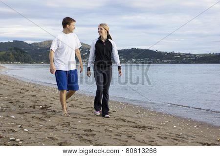 Two friends talking and walking along beach together