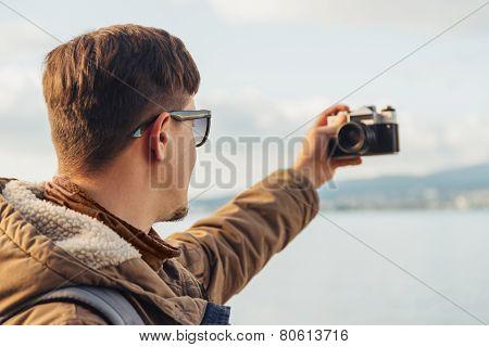Hiker Man Takes Photographs Self Portrait On Coastline