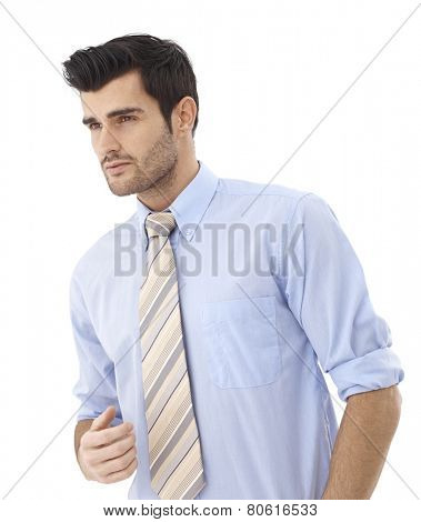 Portrait of handsome young businessman in shirt and tie looking away.