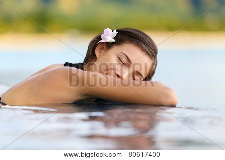 Relaxing woman in luxury hotel pool on holidays - vacation travel. Asian young female person sleeping in pool spa at hotel resort in an exotic getaway.