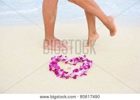Beach wedding just married couple kissing with feet in background and rings in focus in heart shape lei flower necklace. Hawaiian marriage love concept.