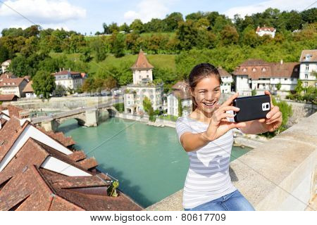 Travel selfie smart phone by woman in Bern Switzerland, Europe. Happy smiling multiracial Asian girl taking self portrait photo sitting on Nydegg bridge by the Aare river in the Swiss city of Berne