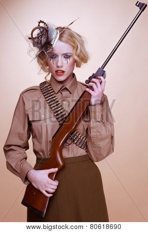 Fashionable Blond Girl Scout Holding Rifle, Isolated on Light Brown Background.