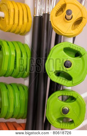 Colorful new weights for bodybuilding in a gym or shop hanging on rods in different sizes and weights