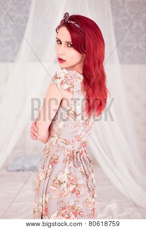 Sexy young redhead woman with a sultry expression standing in front of the mosquito net on her bed in a floral summer dress looking seductively back over her shoulder at the camera