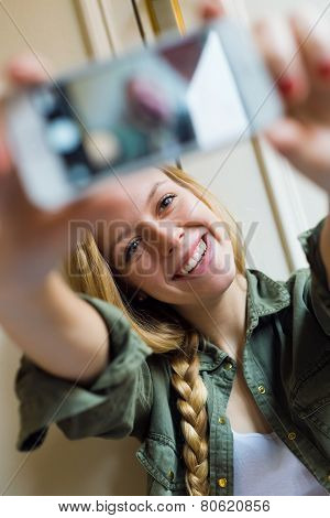 Young Beautiful Woman Taking A Selfie With Smartphone In Her New Home.