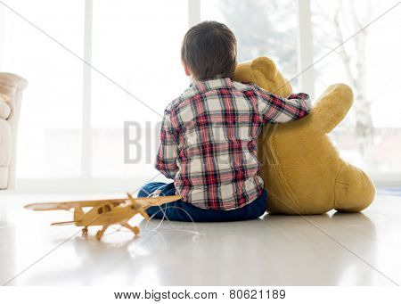 Portrait of child sitting in living room with Teddy bear
