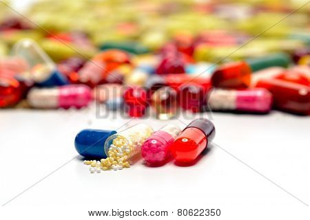 various colorful pills against white background