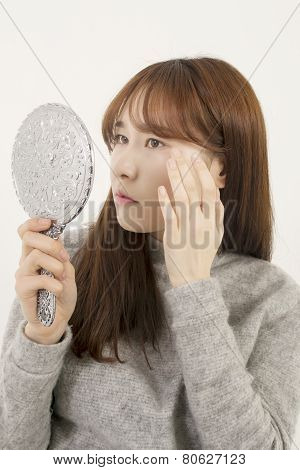 Woman inspecting her skin with a mirror