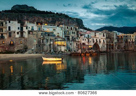Old Boat And Houses In Cefalu At Dusk