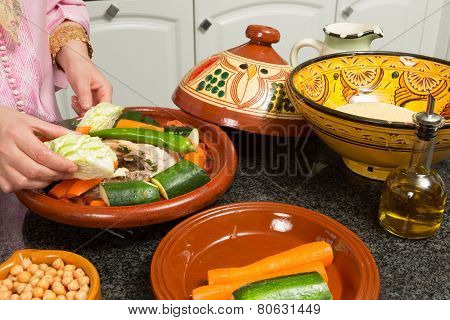 Hands of a woman preparing couscous and a traditional Moroccan tajine during Ramadan nights (Moroccan immigrant woman in modern European kitchen)